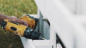 Het gebruiks elektrische schroevedraaier van de arbeidershand aan assamble houten structuur op gras stock videobeelden