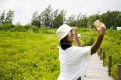Het gebruikssmartphone van de reizigers neemt Thaise vrouw foto op houten brug F Stock Afbeeldingen