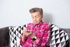 Het gebruikstechnologie van de thema oude persoon de oude grijs-haired Kaukasische vrouw met rimpels zit huis in woonkamer op ban stock fotografie