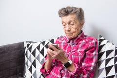 Het gebruikstechnologie van de thema oude persoon de oude grijs-haired Kaukasische vrouw met rimpels zit huis in woonkamer op ban royalty-vrije stock afbeeldingen