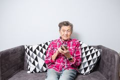 Het gebruikstechnologie van de thema oude persoon de oude grijs-haired Kaukasische vrouw met rimpels zit huis in woonkamer op ban royalty-vrije stock foto's