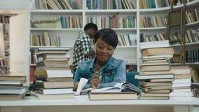 Het geconcentreerde Afrikaanse boek van de vrouwenlezing in de bibliotheek stock footage