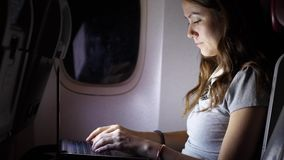 Het geconcentreerde bedrijfsvrouwenwerk aangaande computer in vliegtuig stock videobeelden