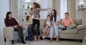 Het geconcentreerde en opgewekte spelen op een videospelletjebroer en een zusteroma en moeder die hen bekijken en ondersteunend a stock video