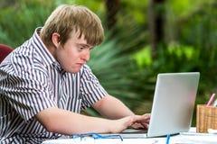 Het geconcentreerde gehandicapte jongen typen op laptop Stock Afbeelding