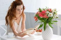 het geconcentreerde jonge boek van de vrouwenlezing terwijl het zitten bij lijst met koffie vormt en bloemen tot een kom royalty-vrije stock fotografie