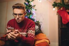 Het geconcentreerde mannetje maakt een aankoop op Internet via een telefoon stock afbeelding