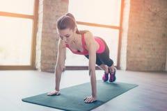 Het geconcentreerde meisje die haar plank doen werkt uit om abs pasvorm te houden zij royalty-vrije stock foto
