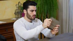 Het geconcentreerde mens spelen met tabletpc stock video