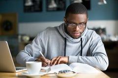 Het geconcentreerde millennial Afrikaanse student maken neemt van terwijl het bestuderen van I nota royalty-vrije stock afbeeldingen