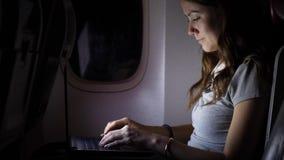 Het geconcentreerde vrouwenwerk aangaande computer in lijnvliegtuig bij nacht stock footage