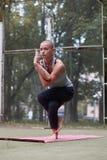 Het geconcentreerde wijfje in yogaadelaar stelt in groen park royalty-vrije stock afbeeldingen