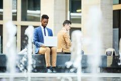 Het geconcentreerde zwarte ondernemer typen op laptop stock foto