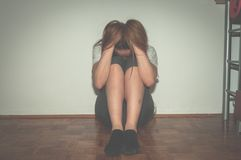 Het gedeprimeerde en eenzame meisje misbruikte als jonge zitting alleen in haar ruimte op vloer miserabel voelen en bezorgdheidss stock fotografie