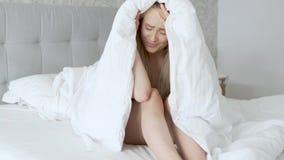 Het gedeprimeerde jonge Kaukasische model stellen op comfortabel die bed in warme deken wordt verpakt stock videobeelden