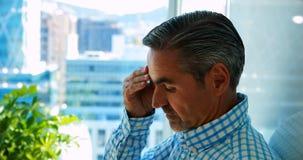 Het gedeprimeerde mannelijke uitvoerende leunen op glasmuur stock video