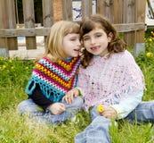 Het gefluister van de zustermeisjes van kinderen in de lente van de oorweide Royalty-vrije Stock Foto's