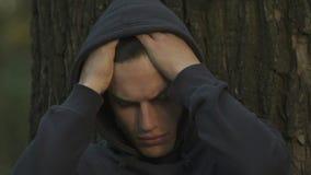 Het gefrustreerde tiener verbergen in park, die aan intimidatie, communicatie problemen lijden stock footage