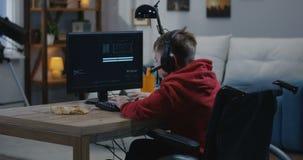 Het gehandicapte jongen binnendringen in een beveiligd computersysteem op zijn computer stock video