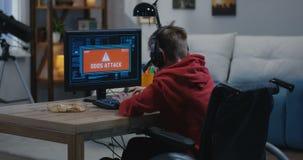 Het gehandicapte jongen binnendringen in een beveiligd computersysteem op zijn computer stock videobeelden
