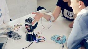 Het gehandicapte meisje opent haar hand en de robothand herhaalt haar bewegingen stock videobeelden