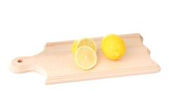 Het geheel en cutted citroen op houten plank Royalty-vrije Stock Foto's