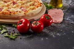 Het geheel en cutted tomaat van pizza op Italiaanse zwarte document lijst Stock Fotografie