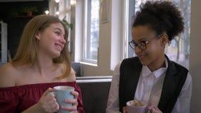 Het geheim van gemengde rasmeisjes, gelukkig Afrikaans Amerikaans tienermeisje zegt het fluisteren roddel aan Kaukasisch meisjeoo stock footage