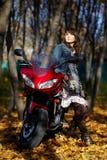 Het geheimzinnige meisje over een rode motorfiets Stock Foto's