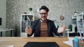 Het gekke beambte typen wat betreft toetsenbord die camera in werkplaats bekijken stock footage