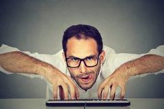 Het gekke kijken het nerdy mens typen op toetsenbord royalty-vrije stock foto's