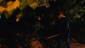 Het gekke mannelijke lopen in donker bos met moordwapen, slachtoffer het verbergen in struiken stock footage