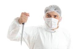 Het gekke medische personeelslid dreigt met een mes in zijn hand; geïsoleerd op witte achtergrond Stock Afbeeldingen