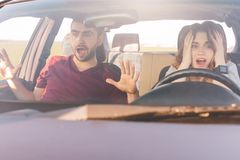 Het gekke wijfje en het mannetje met wanhopige blikken, hebben autoongeval of zijnd uit benzine, verstoorde uitdrukkingen bang ge stock foto's