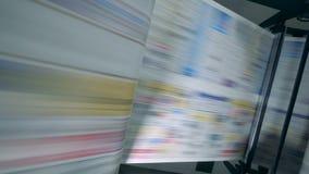 Het gekleurde document die zich op een fabriekstransportband bewegen, sluit omhoog stock videobeelden