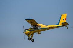 Het gekleurde ultra lichte vliegtuig die bij lucht vliegen toont - geïsoleerd Stock Afbeelding