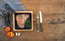 Het gekookte lapje vlees van de vleesrib met knoflookkruidnagels, tomaten, rozemarijn, peper en zout in kleine kokende pan over r Stock Afbeeldingen