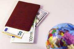 Het geld binnen het paspoort en de bol is uit nadruk 2 stock foto's