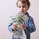 Het geld is de beste motivatie De dollarsbankbiljetten van een kindholding Stock Afbeeldingen