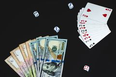 Het geld, dobbelt en kaarten op een zwarte achtergrond Close-up stock afbeelding