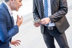 Het geld en de corruptie van de zakenmanbehoefte stock fotografie