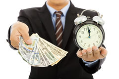 Het geld en de klok van de zakenmanholding De tijd is geldconcept Stock Foto