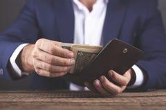 Het geld en de portefeuille van de mensenhand stock foto's