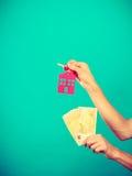 Het geld en de sleutels van de persoonsholding tot huis Stock Foto's