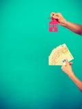 Het geld en de sleutels van de persoonsholding tot huis Stock Afbeelding