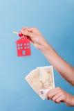 Het geld en de sleutels van de persoonsholding tot huis Royalty-vrije Stock Foto