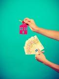 Het geld en de sleutels van de persoonsholding tot huis Stock Fotografie