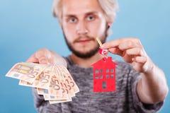 Het geld en de sleutels van de mensenholding tot huis Stock Foto
