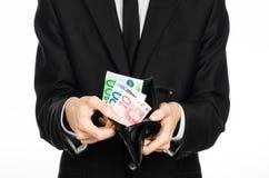 Het geld en de zaken als thema hebben: een mens in een zwart kostuum die een beurs met papiergeldeuro houden die op witte achterg Stock Afbeeldingen