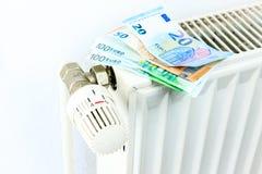 Het geld op een radiator symboliseert de dure verwarmingskostennen royalty-vrije stock fotografie